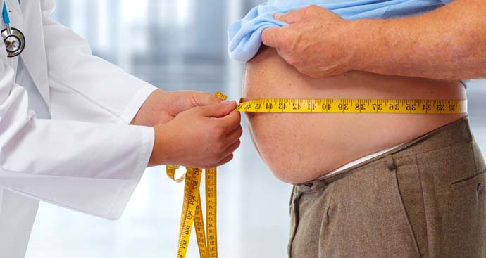 doctor measures the waist fo a man who has been on a weight loss program