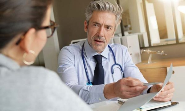 doctor talking with patient in office about weight loss program