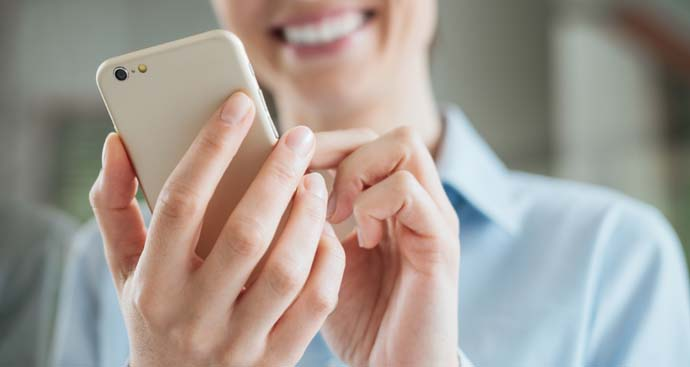 a woman with a smile is using her iPhone to schedule a weight loss consultation
