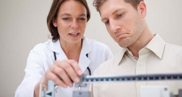 female doctor and patient looking at scale during weight loss appointment
