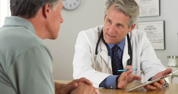 doctor at a desk having a serious conversation with a male patient about his weight and the weight loss program