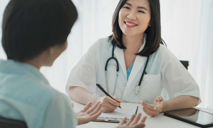 female doctor smiling and looking at a patient during a weight loss consultation